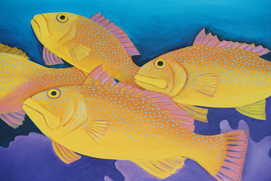 An image of a school of bright orange fish with blue dots