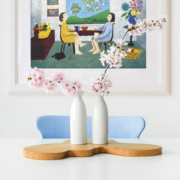 the print of drinking coffee in a home decore setting with some pink flowers