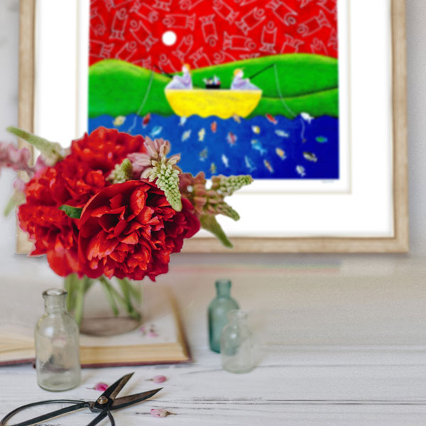 the print styled in a natural timber frame next to bright red flowers matching the red in the picture