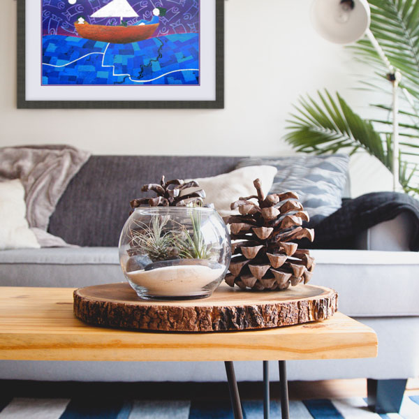 A print of the coloured pencil drawing Sailing Through Life in a dark grey frame matching a grey couch