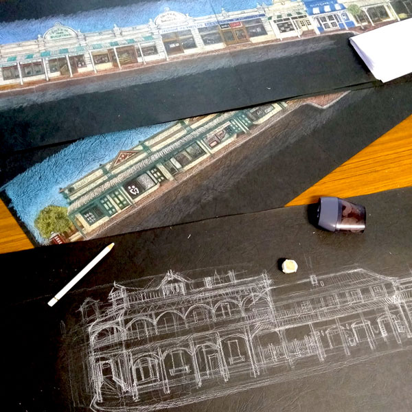 a progress photograph of Mandy drawing historical York buildings - half way through